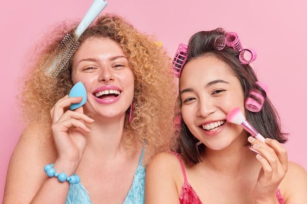 Close-up shot van vrolijke jonge vrouwen van gemengd ras die foundation of poeder op het gezicht aanbrengen met een spons en cosmetische borstelglimlach die in grote lijnen kapsel verzorgen over schoonheid geïsoleerd over roze achtergrond