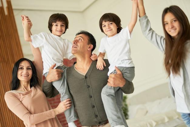 Close-up shot van vrolijke latijns-familie, ouders, tienermeisje en kleine tweelingjongens glimlachend in de camera, hand in hand terwijl ze samen thuis poseren. familie, kindertijd concept
