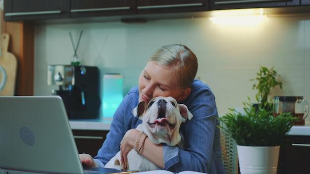 Close-up shot van vrolijke vrouw knuffelen kleine hond in de keuken