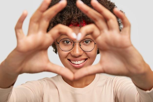 Close-up shot van vrolijke zorgeloze charmante donkere huid meisje maakt hart vorm hand teken over gezicht