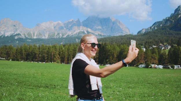 Close-up shot van vrouw videogesprek vanuit prachtige natuurpark tegenover bergen. ze deelt indrukken van haar reis.