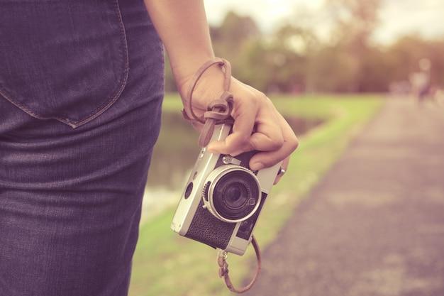 Close-up shot van vrouwelijke hand met retro camera. jonge hipster meisje fotograaf met filmcamera - vintage filter kleur effect stijl