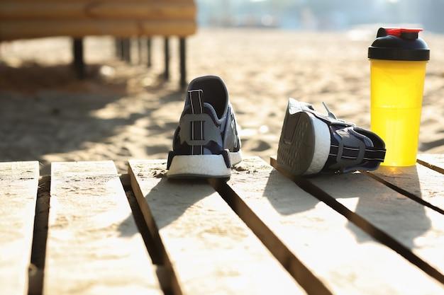 Close-up shot van vrouwelijke sportschoenen en waterfles staande op het strand. ruimte voor tekst