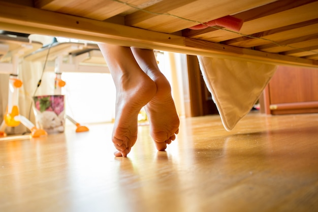 Close-up shot van vrouwelijke voeten onder bed 's ochtends