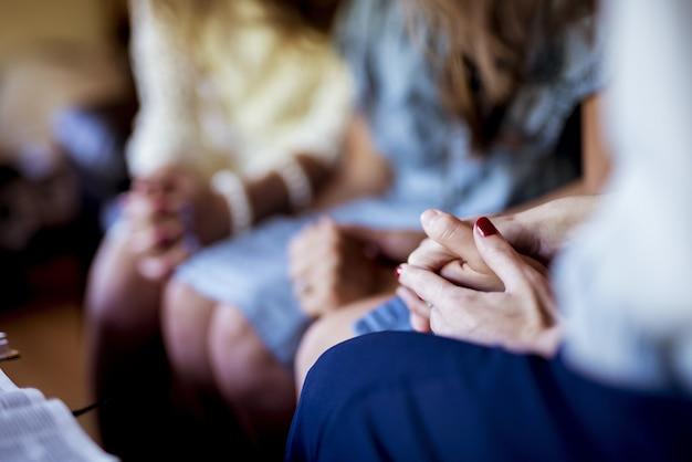 Close-up shot van vrouwtjes zitten terwijl hand in hand en bidden
