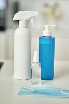 Close-up shot van wasmiddelen sanitizer spray en gel in flessen beschermend gezichtsmasker op keuken