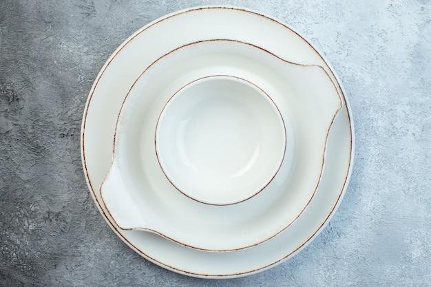 Close-up shot van wit servies op een half donker lichtgrijs oppervlak met een verontrust oppervlak