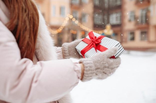 Close-up shot van witte geschenkdoos met een rood lint in de handen van een vrouw, het dragen van warme wollen handschoenen buiten in een winters besneeuwd park. valentijnsdag, kerstmis en winter