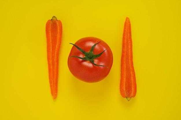 Close-up shot van wortelen en tomaat geïsoleerd op geel.