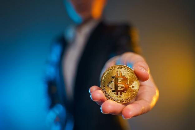 Close-up shot van zakenvrouw in zwart pak met gouden munt geïsoleerd op de achtergrond.