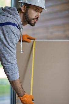 Close-up shot van zelfverzekerde jonge mannelijke bouwer in harde hoed die gipsplaat meet terwijl hij werkt