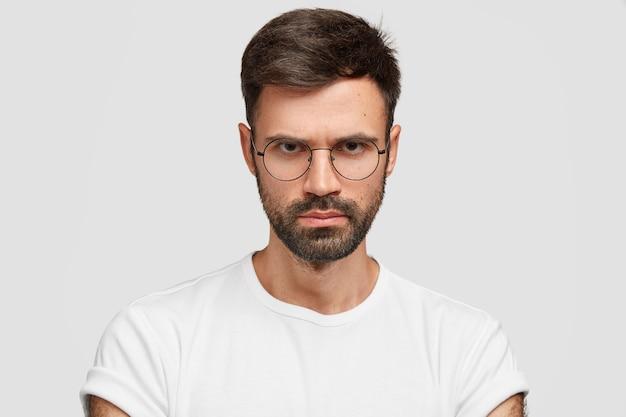 Close-up shot van zelfverzekerde strikte zakenman heeft dikke haren, kijkt met sombere uitdrukking, fronsend gezicht