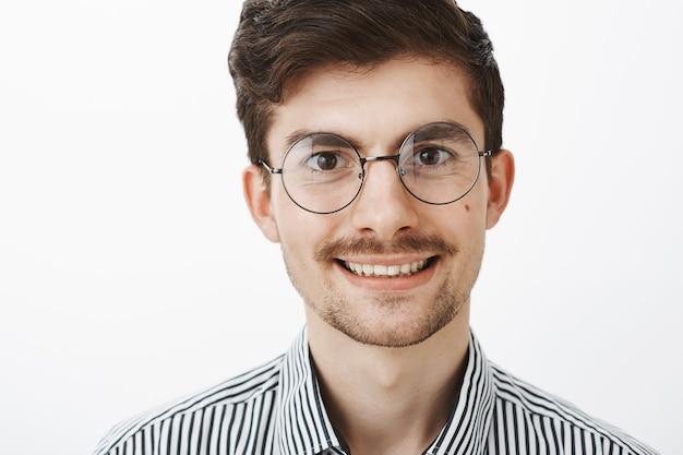 Close-up shot van zelfverzekerde zorgeloze europese man met baard en snor, trendy bril, breed glimlachend en op zoek met positieve uitdrukking, graag praten met vriend