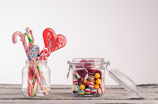 Close-up shot van zuurstokken en andere snoepjes in glazen potten op een houten oppervlak