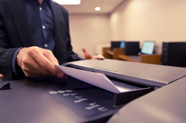Close-up shot zakenlieden zetten papier in de lade van het kopieerapparaat.