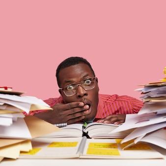 Close-up shot zwarte donkere huid mannelijke wonk dekt mond met hand, kijkt door stapels boeken en papieren, draagt een optische bril voor een goed zicht