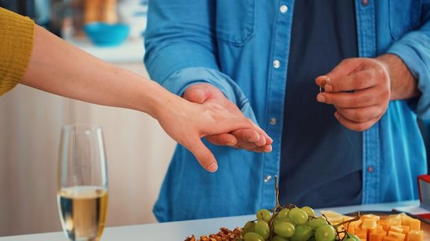 Close-up, slow-motion van de man die de glanzende ring op de vinger van zijn vriendin plaatst terwijl hij in de keuken zit. romantisch gelukkig jong paar in eetkamer, vrouwelijke hand die verlovingsring krijgt
