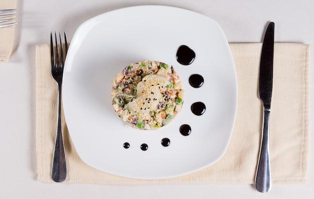 Close-up smakelijk gezond hoofdgerecht van combinatie van zeevruchten, vlees en groenten. geserveerd op een witte plaat op een witte tafel met zilverwerk aan de zijkanten.