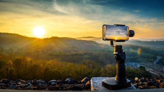 Close-up smartphone neemt een mountian-landschapsfoto en -video op stand mobiele stabilisator i