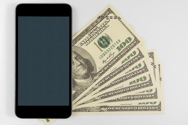 Close-up smartphone op amerikaanse bankbiljetten van honderd dollar