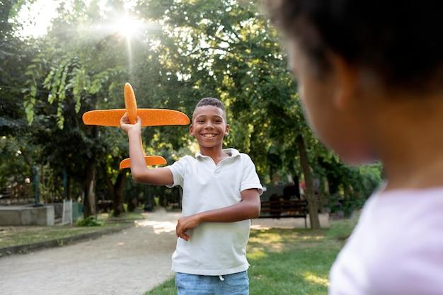 Close-up smiley jongen met vliegtuig