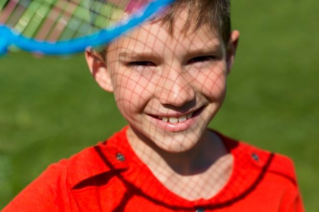 Close-up smiley kind met badmintonracket