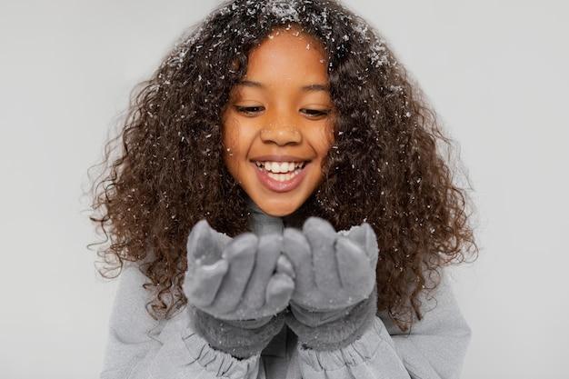 Close-up smiley meisje handschoenen dragen