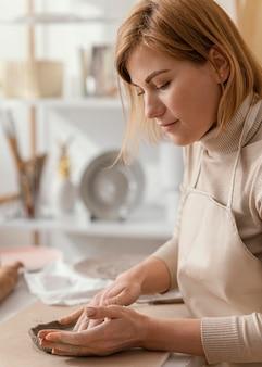 Close-up smiley vrouw binnenshuis aardewerk doen