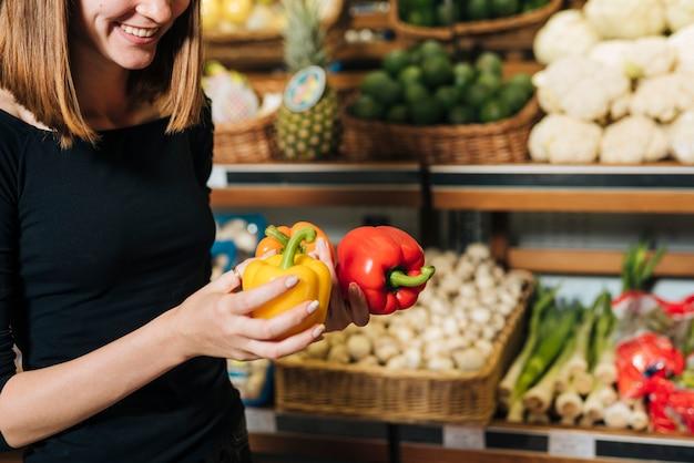 Close-up smiley vrouw met groene paprika's