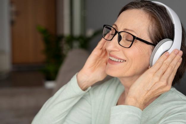 Close-up smileyvrouw die een koptelefoon draagt
