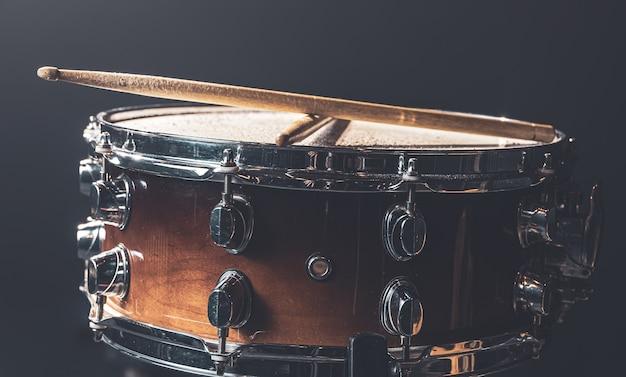 Close-up, snaredrum, percussie-instrument tegen een donkere achtergrond met podiumverlichting.