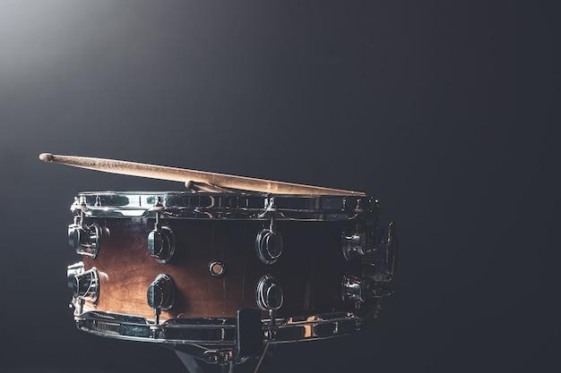 Close-up, snaredrum, percussie-instrument tegen een donkere achtergrond met toneelverlichting, kopieer ruimte.