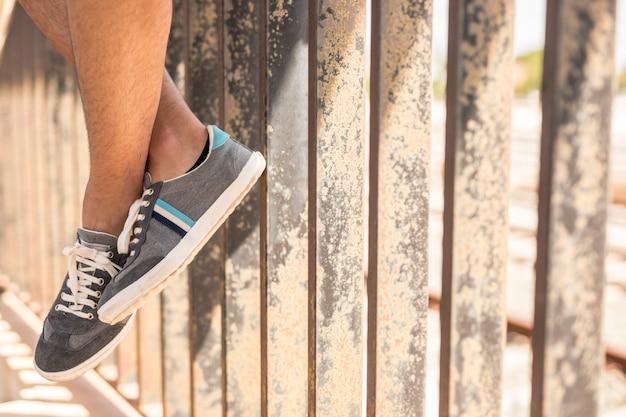 Close-up sneakers met metalen hek