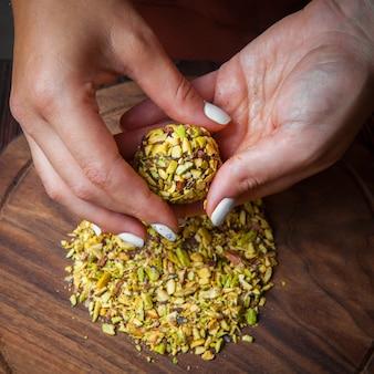 Close-up snoep handgemaakte handgemaakte snoepjes van noten, gedroogde vruchten en honing op een donkere houten ondergrond