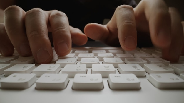 Close-up soft-focus vinger typen op toetsenbord.