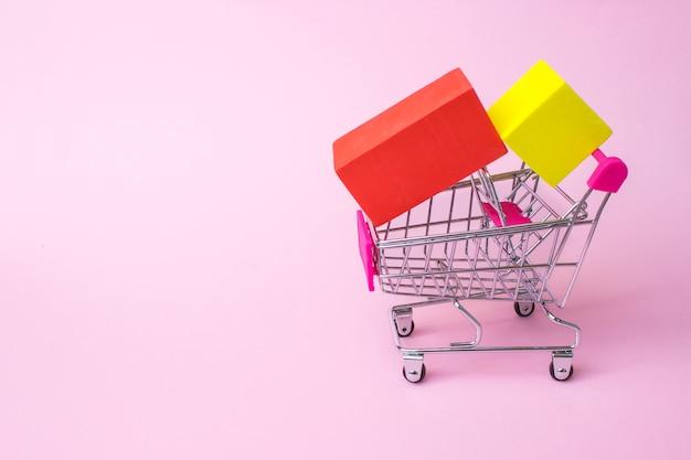 Close-up speelgoed metalen trolley kar met rode plastic handvat rode en gele doos binnen op roze achtergrond