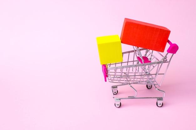 Close-up speelgoed metalen winkelwagentje met rode plastic handvat rode gele doos binnen op roze achtergrond