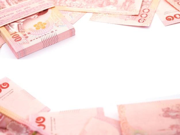 Close-up stapel van thaise 100 baht bankbiljetten op witte achtergrond, bovenaanzicht.
