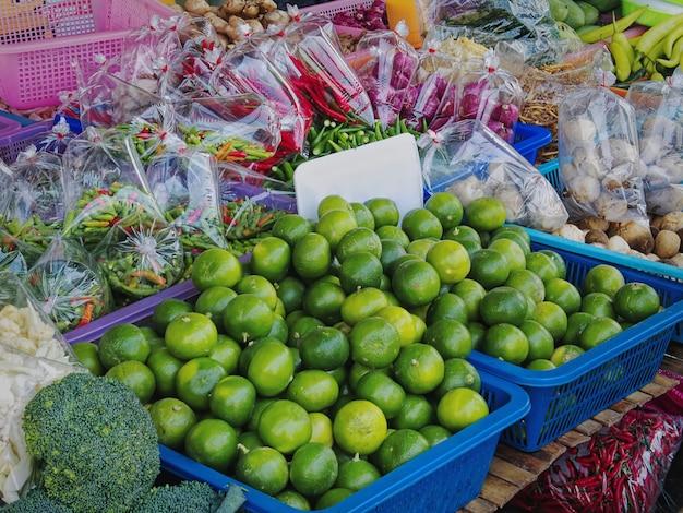 Close-up stapel van verse groene limoenen en verschillende soorten groenten te koop bij marktkraam