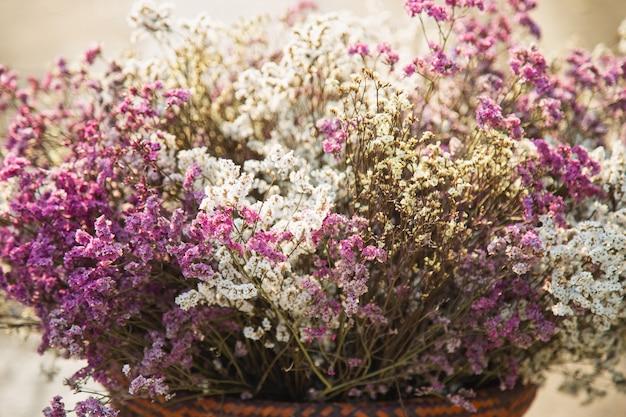 Close-up stelletje gedroogde statice bloemen in een houten mand. romantisch bloemenconcept.