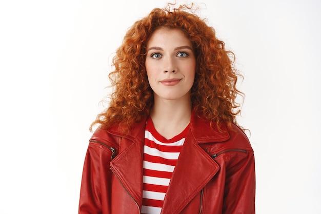 Close-up stijlvolle knappe roodharige millennial meisje wachtrij maken bestelling afhaal hoofd werk kijken trendy dragen rode leren jas make-up glimlachend opgetogen staand gelukkig witte muur
