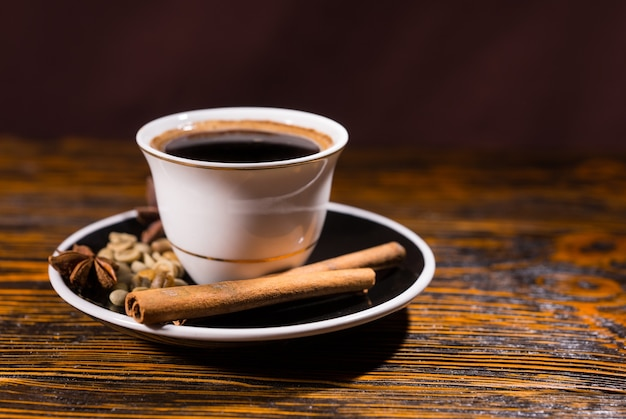 Close-up stilleven van sterke donkere koffie in kopje op schotel gegarneerd met kaneelstokjes, steranijs en andere kruiden op houten tafel met kopie ruimte
