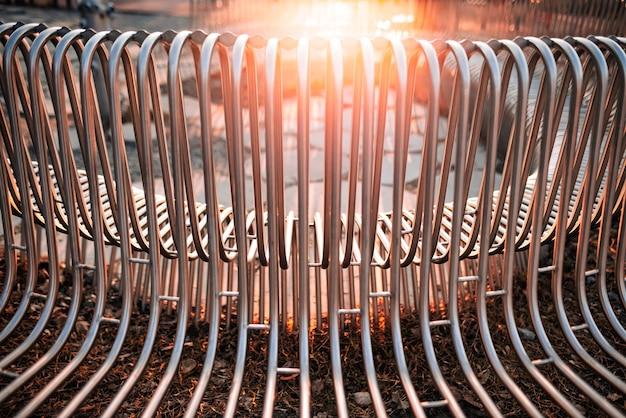 Close-up straatbank metalen buizen evenwijdig aan elkaar gerangschikt op een straatstructuur. concept voor weerbestendige materialen en modern industrieel design.