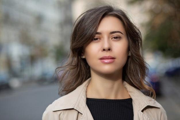 Close-up straatportret van een schattige brunette vrouw met naakte make-up en kort haar die op straat loopt. ruimte voor tekst