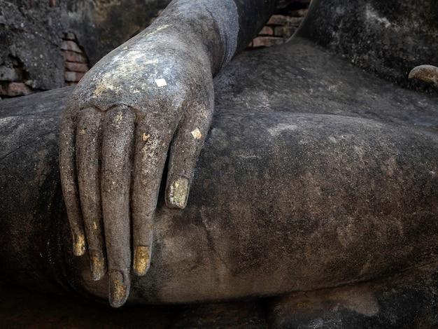 Close-up stucwerk hand van het oude boeddhabeeld bij wat sri chum temple, de beroemde bezienswaardigheid in sukhothai historical park, een unesco world heritage site in thailand.