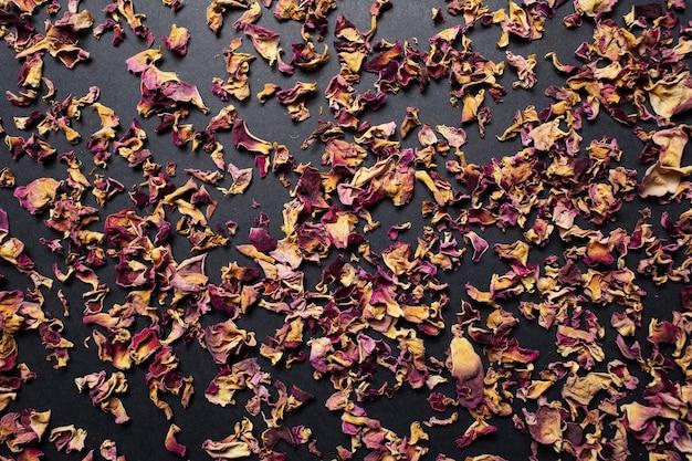 Close-up studio foto van gedroogde thee rozenblaadjes, op de zwarte tafel.
