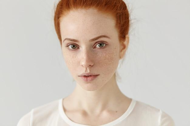 Close-up studio-opname van mooie charmante roodharige europees model met gezonde sproeten huid