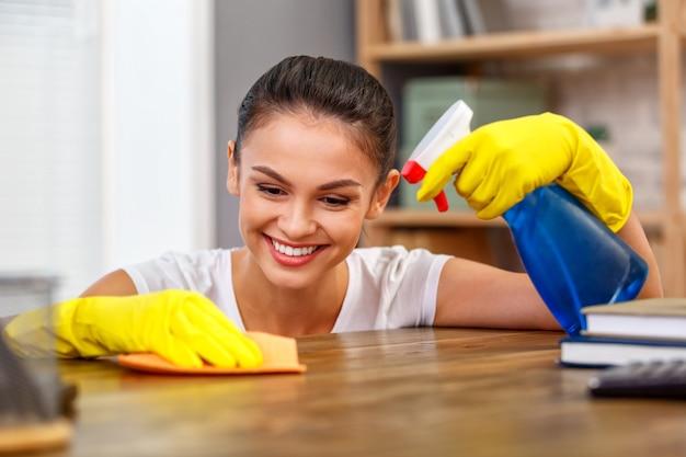 Close-up studio shot van huishoudster. mooie vrouw schoonmaak tafel met spray. vrouw die handschoenen draagt. focus op handen