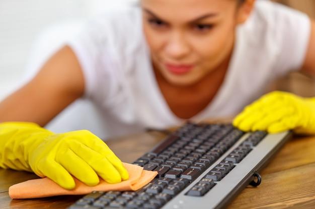 Close-up studio shot van huishoudster. mooie vrouw schoonmaken toetsenbord. vrouw die handschoenen draagt. focus op handen