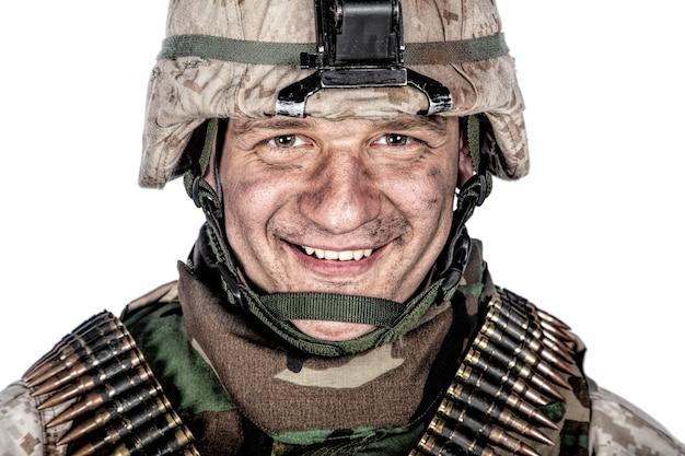 Close-up studioportret van vriendelijk ogende marine, militaire veteraan met vuil of roet op gezicht in haveloze gevechtshelm en munitieriemen over schouders, kijkend naar camera met glimlach, bijgesneden op wit